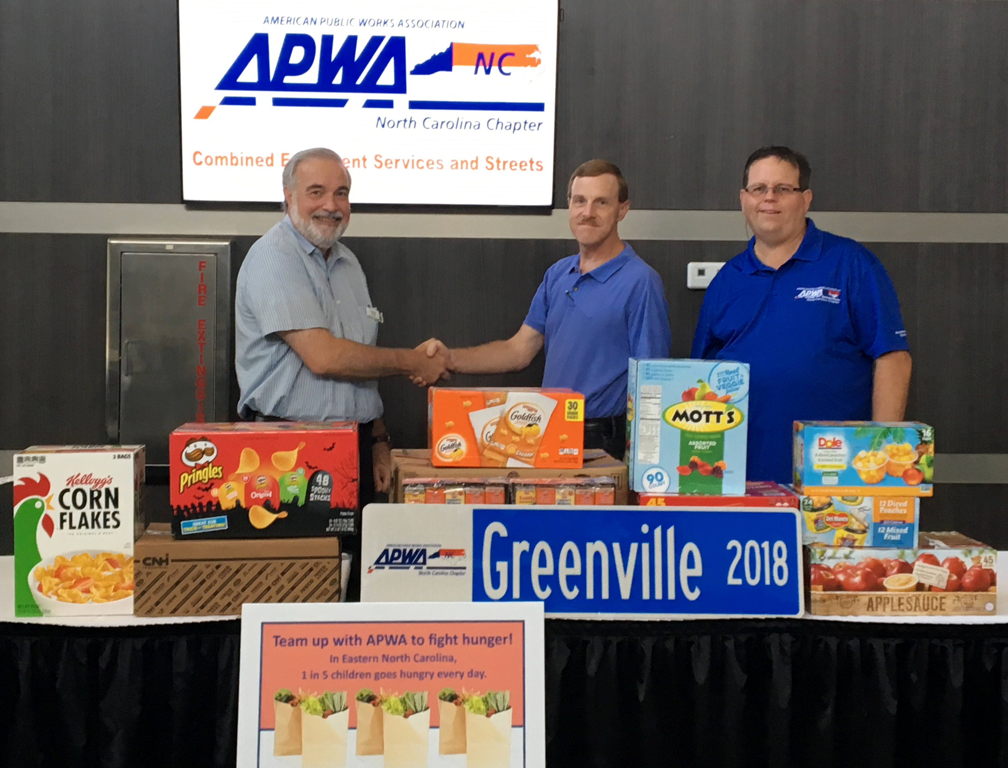 APWA-NC and the Food Bank shake hands near a stack of food donations from the ESS conference September 2018